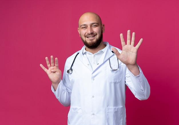 Lächelnder junger männlicher arzt, der medizinische robe und stethoskop trägt, die verschiedene zahlen zeigen, die auf rosa isoliert werden