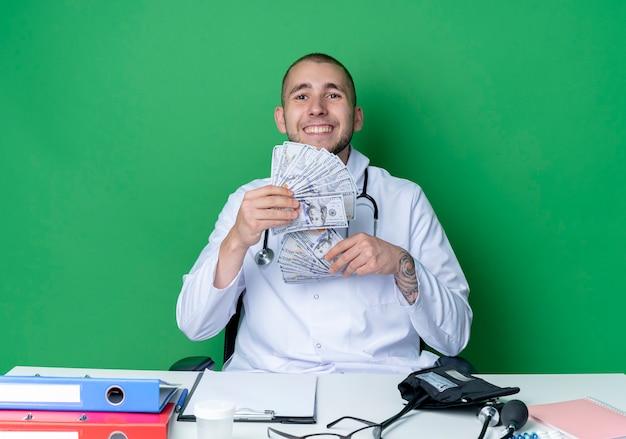 Lächelnder junger männlicher arzt, der medizinische robe und stethoskop trägt, sitzt am schreibtisch mit arbeitswerkzeugen, die geld lokalisiert auf grüner wand halten