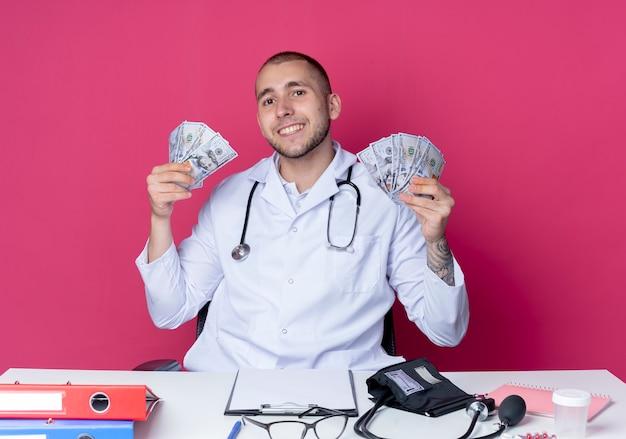 Lächelnder junger männlicher arzt, der medizinische robe und stethoskop trägt, sitzt am schreibtisch mit arbeitswerkzeugen, die geld lokalisiert auf rosa wand halten