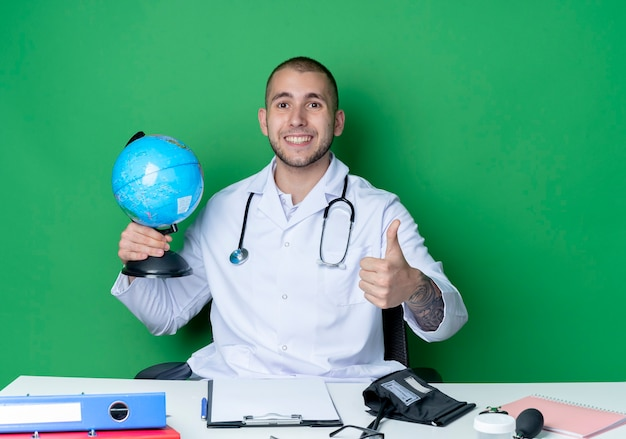 Lächelnder junger männlicher arzt, der medizinische robe und stethoskop trägt, sitzt am schreibtisch mit arbeitswerkzeugen, die globus halten und daumen oben lokalisiert auf grüner wand zeigen