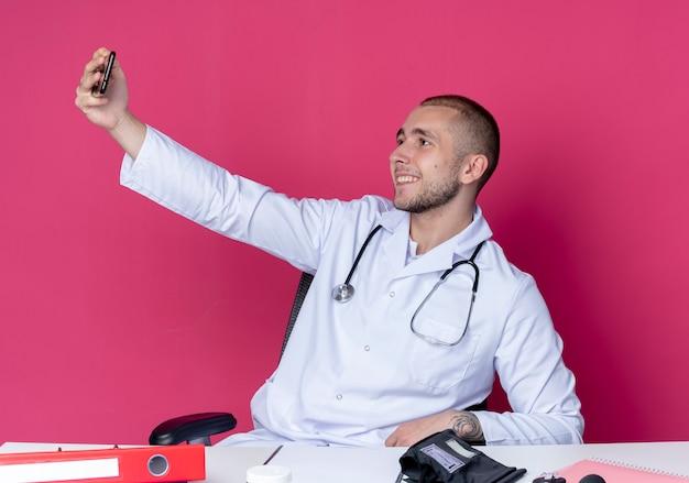 Lächelnder junger männlicher arzt, der medizinische robe und stethoskop trägt, sitzt am schreibtisch mit arbeitswerkzeugen, die selfie lokalisiert auf rosa wand nehmen