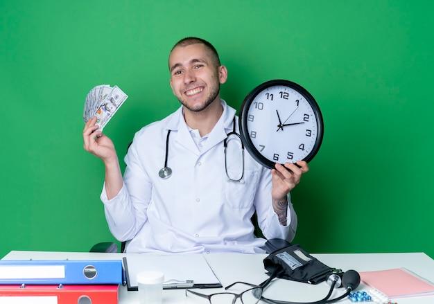 Lächelnder junger männlicher arzt, der medizinische robe und stethoskop trägt, sitzt am schreibtisch mit arbeitswerkzeugen, die uhr und geld lokalisiert auf grüner wand halten