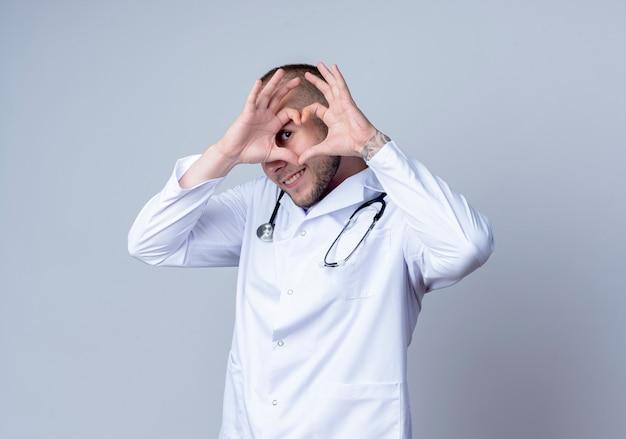 Lächelnder junger männlicher arzt, der medizinische robe und stethoskop um seinen hals trägt, das herzzeichen tut und vorne durch sie lokalisiert auf weißer wand betrachtet