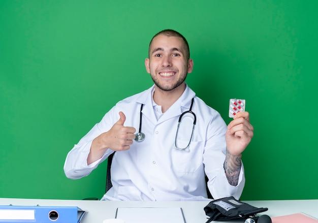 Lächelnder junger männlicher arzt, der medizinisches gewand und stethoskop trägt, sitzt am schreibtisch mit arbeitswerkzeugen, die packung der kapseln halten und daumen oben lokalisiert auf grüner wand zeigen