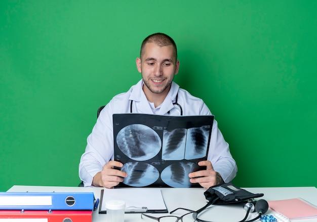 Lächelnder junger männlicher arzt, der medizinisches gewand und stethoskop trägt, sitzt am schreibtisch mit arbeitswerkzeugen, die röntgenaufnahme lokalisiert auf grüner wand halten und betrachten