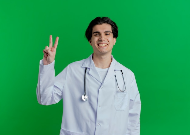 Lächelnder junger männlicher arzt, der medizinisches gewand und stethoskop tut friedenszeichen lokalisiert auf grüner wand mit kopienraum trägt