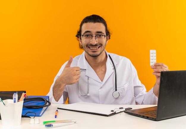 Lächelnder junger männlicher arzt mit medizinischer brille, der ein medizinisches gewand mit stethoskop trägt, das am schreibtisch sitzt
