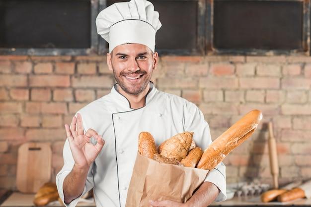 Lächelnder junger männlicher bäcker, der das okayzeichen hält brotlaib zeigt