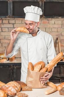 Lächelnder junger männlicher bäcker, der frisches hörnchen mit broten riecht