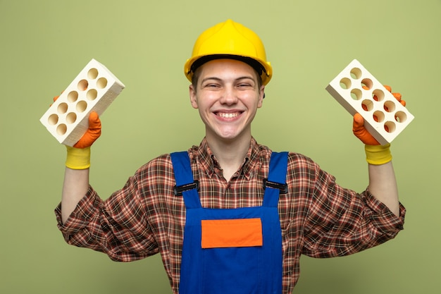 Lächelnder junger männlicher baumeister, der uniform mit handschuhen trägt, die ziegelsteine halten