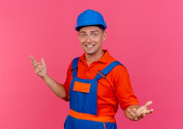 Lächelnder junger männlicher baumeister, der uniform und schutzhelm trägt, breitet hände aus
