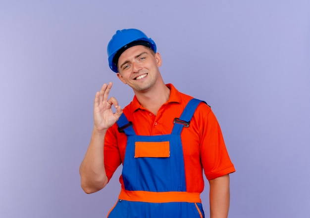Lächelnder junger männlicher baumeister, der uniform und schutzhelm trägt, die okey geste auf purpur zeigen