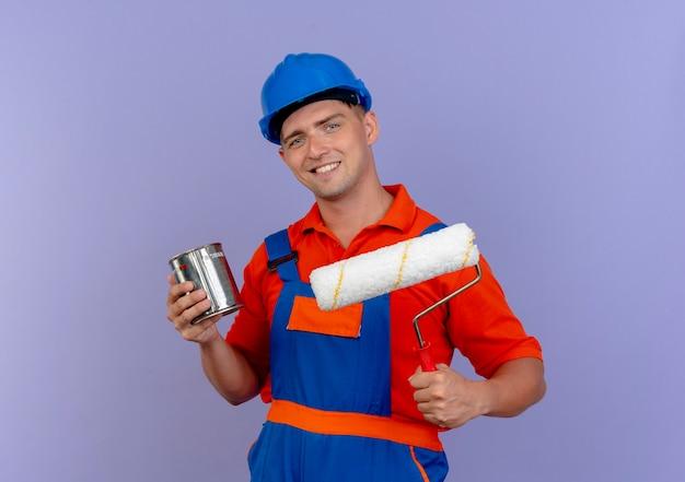 Lächelnder junger männlicher baumeister, der uniform und sicherheitshelm hält, der farbdose und farbroller auf purpur hält