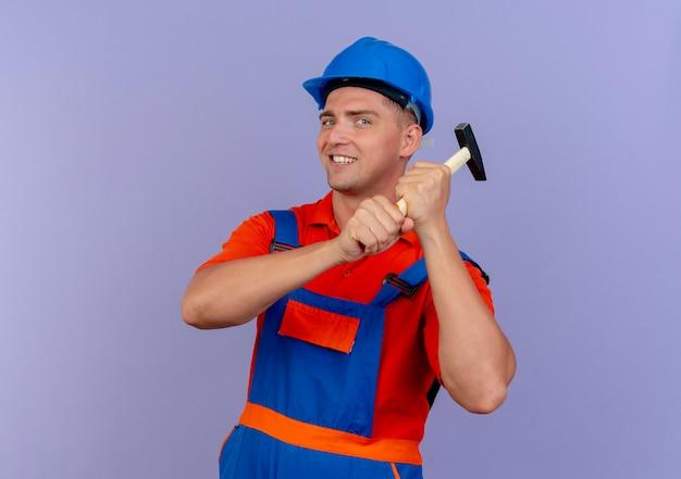 Lächelnder junger männlicher baumeister, der uniform und sicherheitshelm trägt, der hammer um schulter auf purpur hält