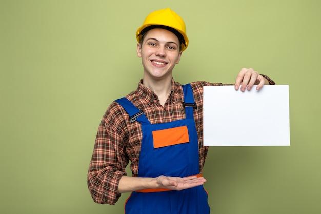 Lächelnder junger männlicher baumeister hält und zeigt mit handpapier in uniform