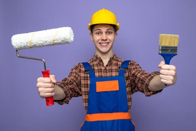 Lächelnder junger männlicher baumeister in uniform, der pinsel mit walzenbürste hält