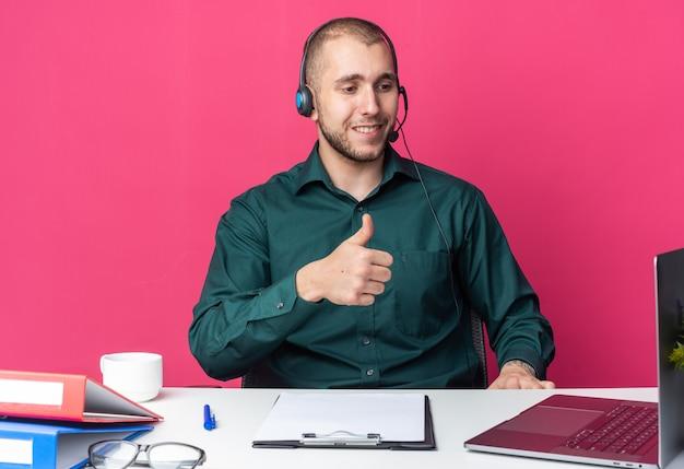 Lächelnder junger männlicher callcenter-betreiber mit headset am schreibtisch sitzend mit bürowerkzeugen, die auf den laptop schauen, der daumen nach oben zeigt