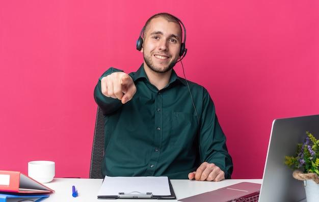 Lächelnder junger männlicher callcenter-betreiber mit headset am schreibtisch sitzend mit bürowerkzeugen, die ihnen gesten zeigen