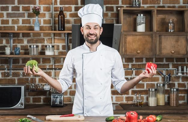 Lächelnder junger männlicher chef, der brokkoli und roten grünen pfeffer in seinen händen hält