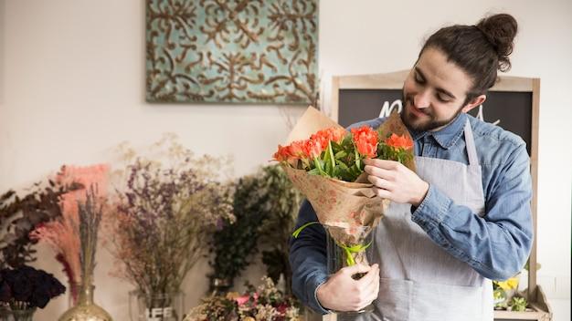 Lächelnder junger männlicher florist, der blumen im blumenstrauß betrachtet