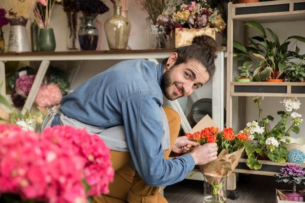 Lächelnder junger männlicher florist, der die blume im blumenstrauß vereinbart