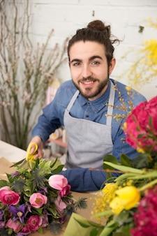 Lächelnder junger männlicher florist, der die kamera macht den blumenblumenstrauß betrachtet