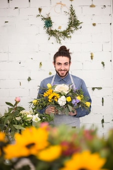 Lächelnder junger männlicher florist, der in der hand den blumenblumenstrauß gegen ziegelsteinweißwand hält