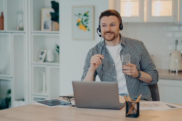 Lächelnder junger männlicher freiberufler im headset, der an online-meetings oder webkonferenzen auf dem laptop teilnimmt, ein glas wasser und einen stift hält, während er zu hause arbeitet. remote-job-konzept