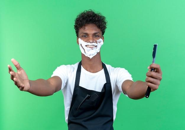 Lächelnder junger männlicher friseur, der uniform mit rasierschaum trägt