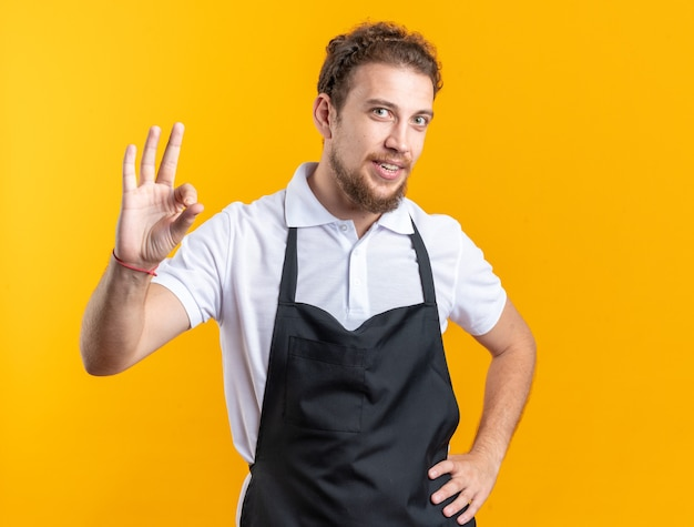 Lächelnder junger männlicher friseur in uniform, der eine gute geste zeigt, die die hand auf die hüfte legt, isoliert auf gelbem hintergrund
