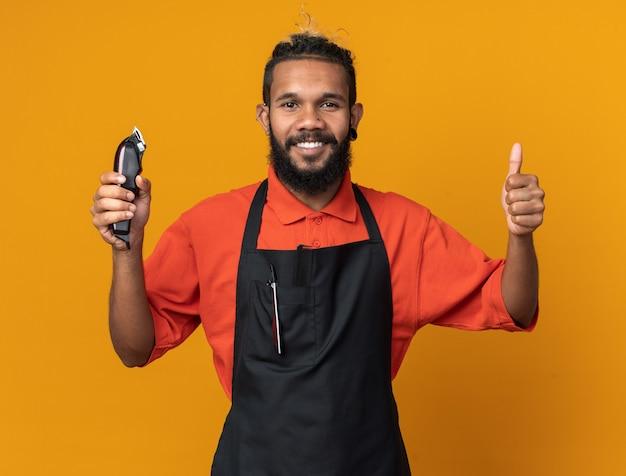 Lächelnder junger männlicher friseur in uniform, der haarschneidemaschinen hält und nach vorne schaut, der daumen nach oben isoliert auf oranger wand zeigt