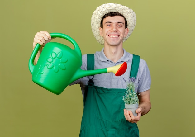 Lächelnder junger männlicher gärtner, der gartenhut trägt, gibt vor, blumen im blumentopf mit gießkanne zu gießen