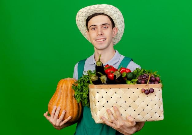 Lächelnder junger männlicher gärtner, der gartenhut trägt, hält kürbis und gemüsekorb suchen