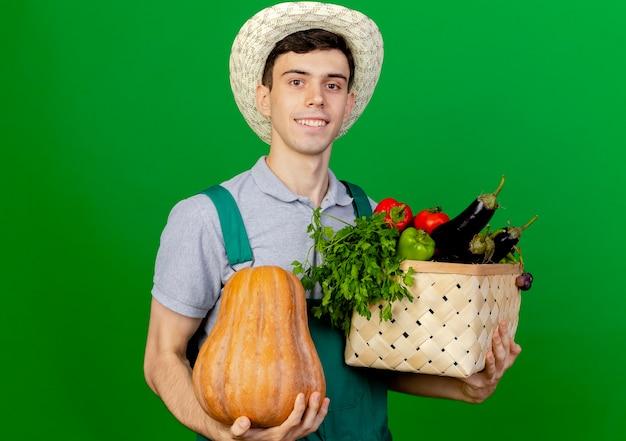 Lächelnder junger männlicher gärtner, der gartenhut trägt, hält kürbis und gemüsekorb