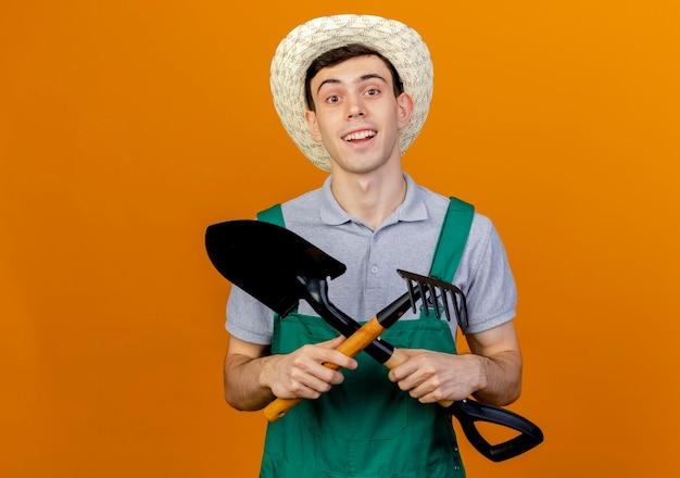 Lächelnder junger männlicher gärtner, der gartenhut trägt, kreuzt spaten und rechen
