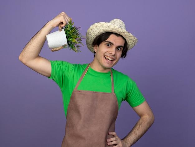 Lächelnder junger männlicher gärtner in der uniform, die gartenhut hält, der blume im blumentopf hält, der starke geste zeigt, die hand auf hüfte setzt