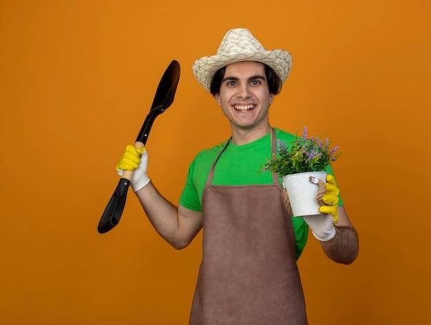 Lächelnder junger männlicher gärtner in der uniform, die gartenhut mit handschuhen hält, die spaten mit blume im blumentopf halten, lokalisiert auf orange wand