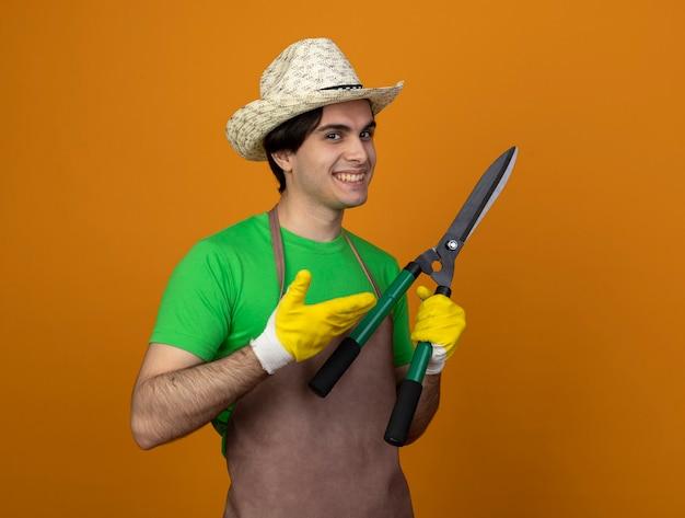 Lächelnder junger männlicher gärtner in der uniform, die gartenhut mit handschuhen hält und mit hand auf schermaschinen zeigt