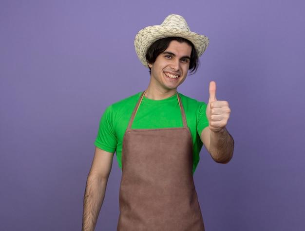 Lächelnder junger männlicher gärtner in der uniform, die gartenhut trägt, der daumen oben zeigt