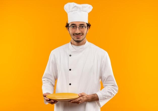 Lächelnder junger männlicher koch, der die kochuniform und die brille hält, die platte lokalisiert auf gelber wand tragen