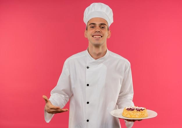 Lächelnder junger männlicher koch, der kochuniform hält und mit handkuchen auf teller zeigt