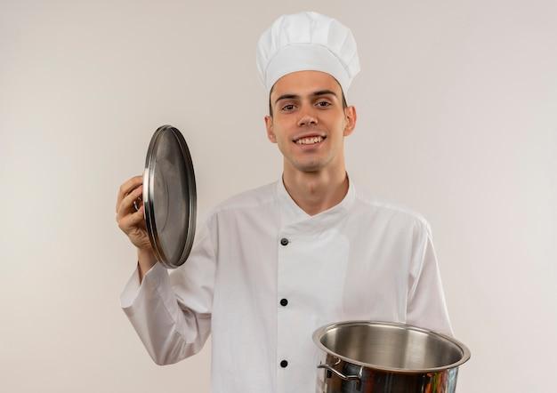 Lächelnder junger männlicher koch, der kochuniform trägt, die topf und deckel hält