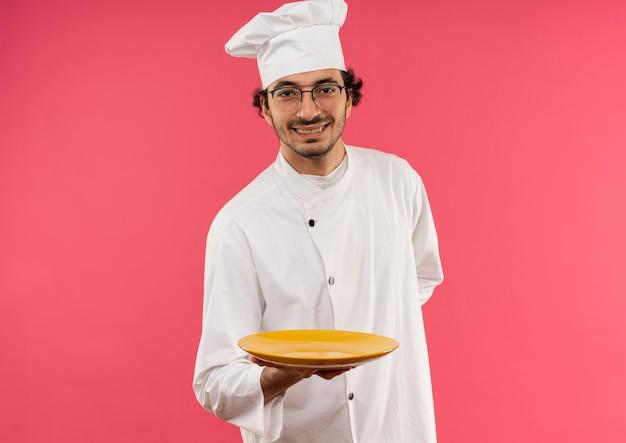 Lächelnder junger männlicher koch, der kochuniform und brille hält platte trägt