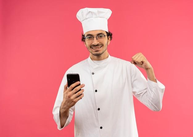 Lächelnder junger männlicher koch, der kochuniform und brille hält telefon hält und starke geste tut, die auf rosa wand lokalisiert wird
