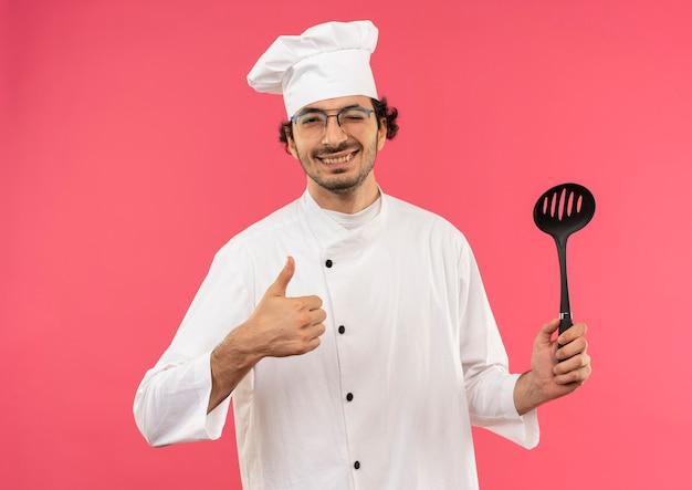 Lächelnder junger männlicher koch, der kochuniform und brille trägt, hält spatel seinen daumen hoch