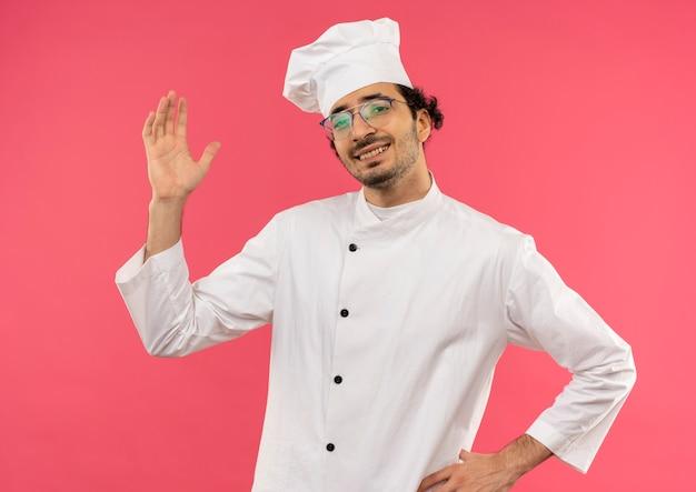 Lächelnder junger männlicher koch, der kochuniform und brille trägt hand hebt und eine andere hand auf hüfte auf rosa legt