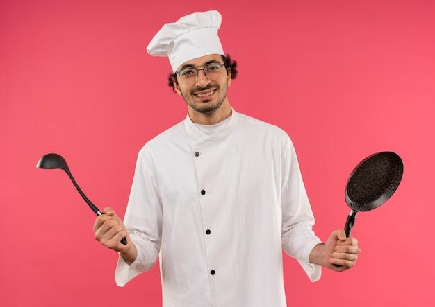 Lächelnder junger männlicher koch, der kochuniform und gläser hält bratpfanne mit kelle auf rosa