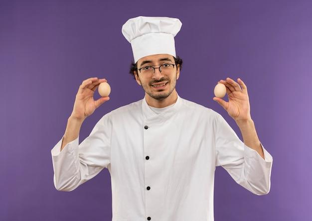 Lächelnder junger männlicher koch, der kochuniform und gläser trägt, die eier auf purpur halten