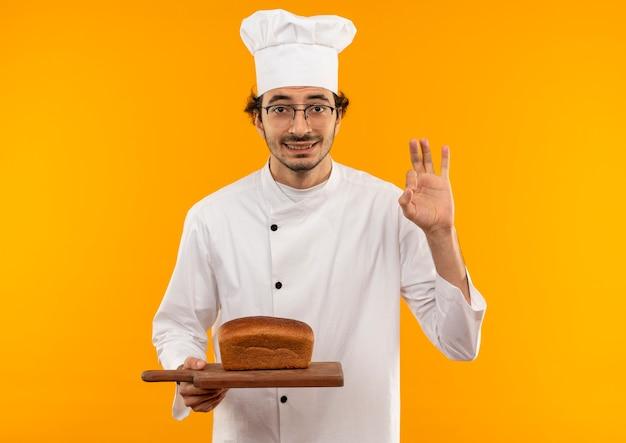 Lächelnder junger männlicher koch, der kochuniform und glasbrot auf schneidebrett trägt, das okey lokalisiert auf gelber wand zeigt