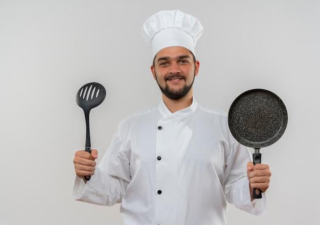 Lächelnder junger männlicher koch in der kochuniform, die geschlitzten löffel und bratpfanne lokalisiert auf weißem raum hält